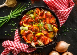 Stewed pepper and sausage with tomatoes in a cast iron skillet on a black background, top view. Traditional Hungarian stew called lecho
