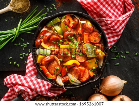 Stewed pepper and sausage with tomatoes in a cast iron skillet on a black background, top view. Traditional Hungarian stew called lecho  Foto d'archivio ©
