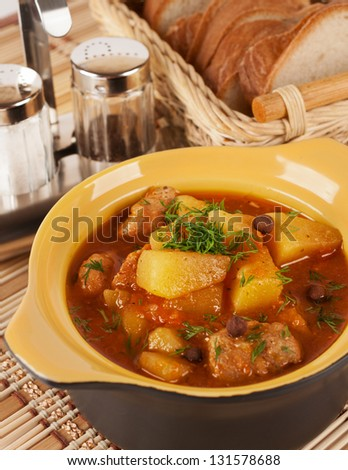 Stewed potatoes with meat in a ceramic pot.