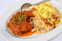 Stewed rooster in tomato sauce, served with homemade pasta and cheese. Traditional Greek dish