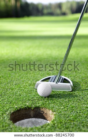 Stick pushes the ball in the hole