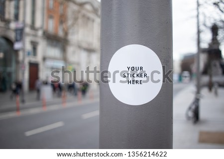 Sticker Mockup on a street lamp in a busy city street