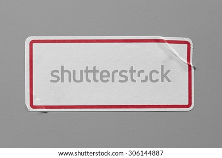 Stickers Label Close Up on Grey Background with Real Shadow. Top View of Adhesive Paper Tag with a Red Border. Copy Space for Text or Image #306144887