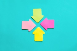 sticky colorful paper arrows pointing at the same direction, to the center
