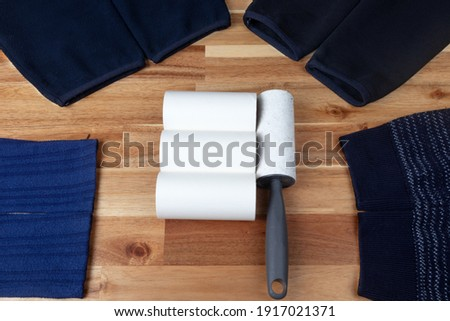 Sticky lint roller and spare tubes on fabric. hair remover. Stockfoto ©