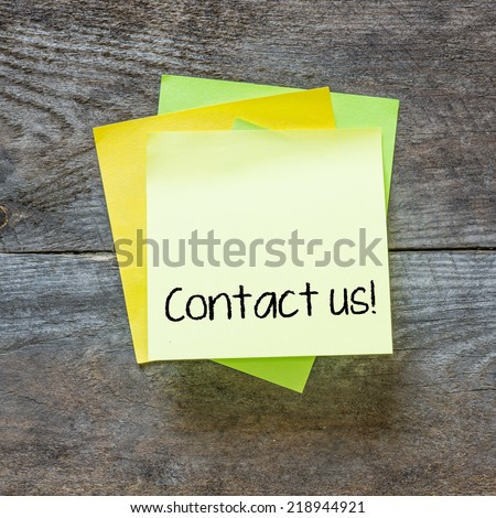 Sticky note on a wooden wall with the words Contact Us on it
