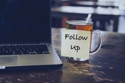 Sticky note with FOLLOW US wording on glass of tea with laptop on wooden table. Motivation and positive wishes concept