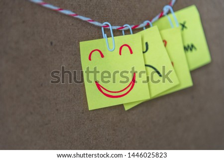 Sticky note with hand drawn a funny smiley face on cork board, with copy space. Positive mood and happy workplace concept. #1446025823