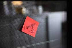 Sticky note with handwritten text I Love You attached to oven door in kitchen. Romantic message