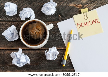 Sticky note with the word deadline. White blank paper, crumpled paper, pen and a cup of coffee on a wooden background