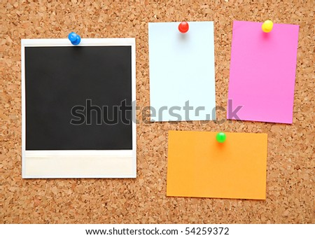 sticky notes and photo frame over brown cork background