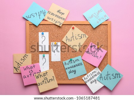 Sticky notes with autism related phrases on cork board #1065187481