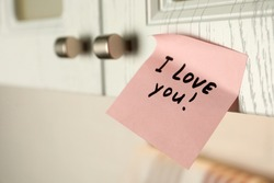 Sticky paper with words I Love You on door of kitchen cabinet indoors, closeup