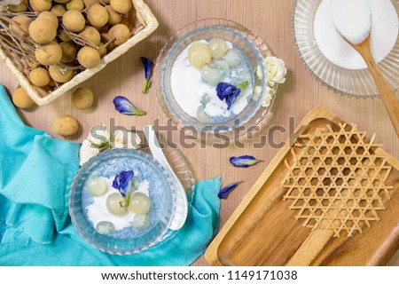 Sticky rice boiled in syrup with longan and coconut milk dressing. Thai dessert