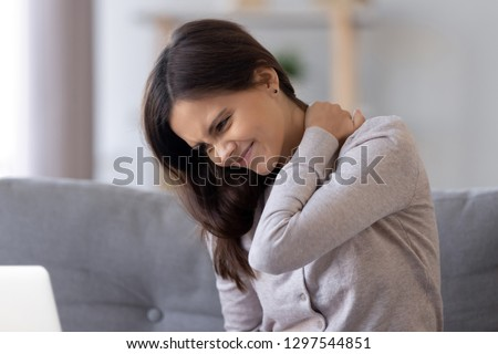 Stiff neck concept, young woman feeling discomfort hurt joint pain rubbing tensed muscles, tired teen girl massaging back to relieve fibromyalgia ache after long computer study in incorrect posture