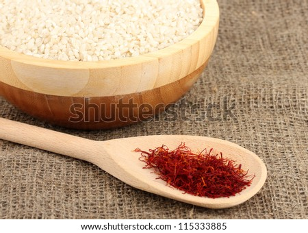 stigmas of saffron in wooden bowl with spoon on canvas background close-up
