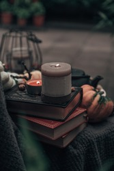 Stil life with books, candles, pumpkin, lantern and a tea pot. Autumn/Fall or Halloween concept.