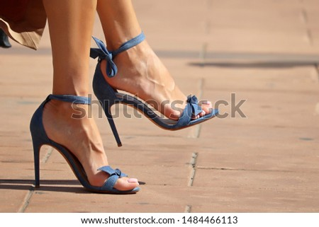 Stiletto heels, female feet in high-heeled summer shoes. Stylish woman with pedicure sitting on a city street in sunny day #1484466113
