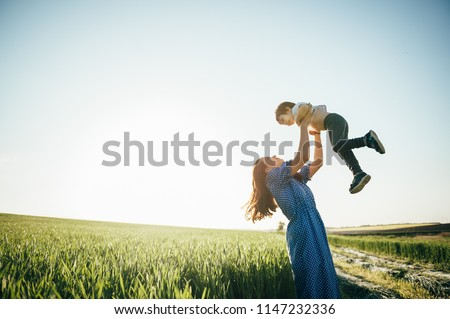 Stilish mother and handsome son having fun on the nature. Happy family concept. Beauty nature scene with family outdoor lifestyle. Happy family resting together. Happiness in family life. Mothers day.