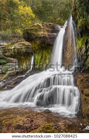 Still beautiful, even with reduced flow in the early fall, Upper Cataract Falls, a waterfall in Owen County, Indiana, spills through and cascades over a mossy limestone cliff. #1027088425