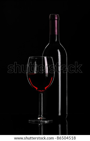 still-life arrangement: bottle of wine and a glass wine on black background
