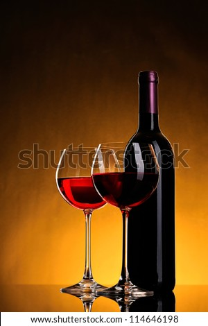 still-life arrangement: bottle of wine and two glasses wine on yellow background