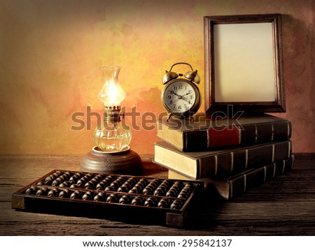 Still life art photography wisdom concept with alarm clock books oil lantern lamps wood abacus on vintage background environment