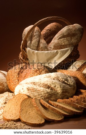 still life assortment of baked bread over brown background