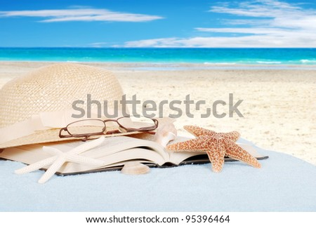 Still life beach concept with book glasses and hat