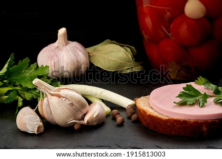 Still life. Boiled sausage sandwich on black bread, head of garlic, onion, parsley, can of canned cherry tomatoes and bay leaf on a slate board. Set. Close-up. Foto stock ©