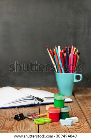 Still life, business, education concept. School supplies and open notebook on a wooden table with chalkboard. Selective focus, copy space, school background #309494849