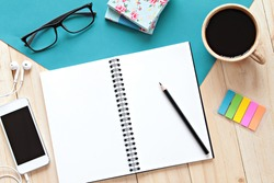 Still life, business, office supplies or education concept : top view image of open notebook with blank pages, mobile phone and coffee cup on wooden background, ready for adding or mock up