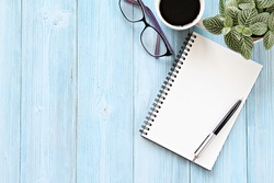 Still life, business, planning or working concept : Open notebook with blank pages, coffee cup and eyeglasses on wooden desk table, top view or flat lay with copy space ready for adding or mock up