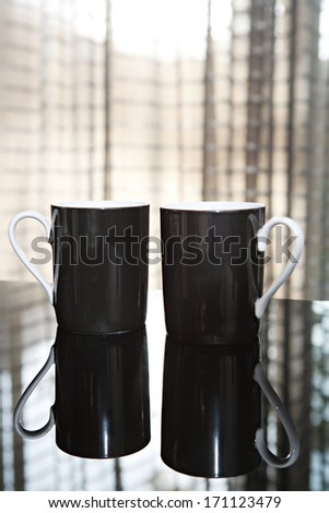 Still life close up detail view of two luxury black tea mugs on a reflective dining table in a quality expensive home with smart curtains. Home interior detail view.