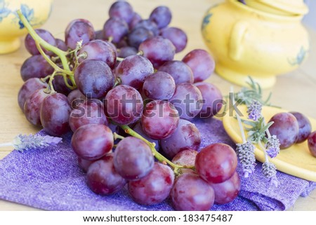 Still life composed of bunch of grapes on purple napkin and wooden table, with different yelow elements and decorated with violet flowers.
