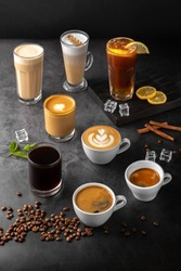 still life composition with glasses and cups of espresso, latte americano, brewed, raf coffee, cappuccino with rosetta latte and green matcha art and roasted coffee beans on a black marble background