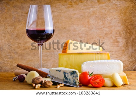 Still life composition with rustic snack food, cheese and red wine