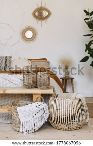 Still life concept. Vertical photo of cozy apartment in boho chic style interior with comfort bedroom, fabric sheet plaid on bed, wooden bench seat, dry plants in vase, home decor in wicker basket Stock photo ©