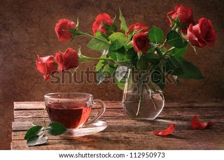 Still-life, Delightful bouquet of scarlet roses and cup of fragrant tea - stock photo