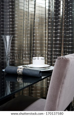 Still life detail view of a luxury home festive diner table set for evening guests. Designer home interior with elegant furniture and tableware. Hotel interior.