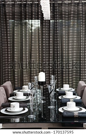 Still life detail view of a luxury home festive diner table set for six evening guests. Designer home interior with elegant furniture and tableware. Hotel interior.