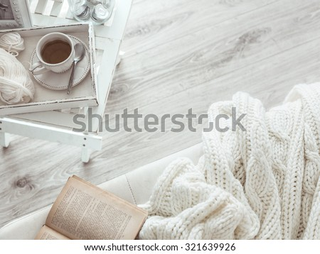 Still life details, cup of tea on retro vintage wooden tray on a coffee table in living room, top view point. Lazy winter weekend with a book on the sofa.