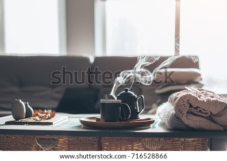 Still life details in home interior of living room. Sweaters and cup of tea with steam on a serving tray on a coffee table. Breakfast over sofa in morning sunlight. Cozy autumn or winter concept.
