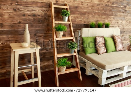 Still life details of cozy home interior in rustic style. Country style living room with wooden stairs and sofa with green and golden pillows. Scandinavian style home decor with rustic wooden boards.