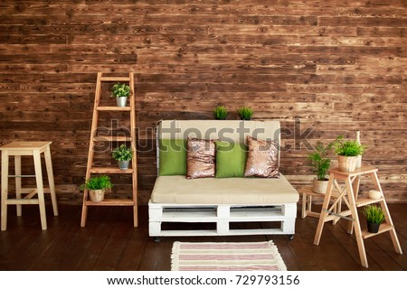 Still life details of cozy home interior in rustic style. Country style living room with wooden stairs and sofa with green and golden pillows. Scandinavian style home decor with rustic wooden boards. #729793156