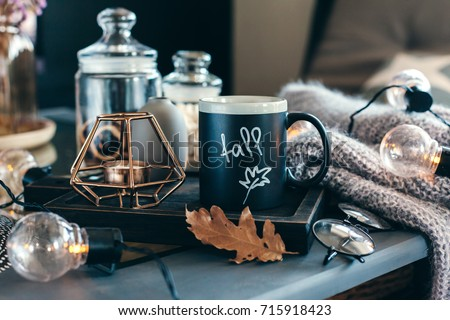 Shutterstock Still life details of living room. Cup of coffee on rustic wooden tray, candle and warm woolen sweater on table, decorated with led lights. Autumn weekend concept. Fall home decoration.