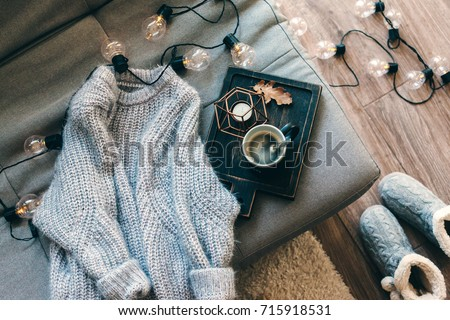 Still life details of living room. Cup of coffee on rustic wooden tray, candle and warm woolen sweater on sofa, decorated with led lights, top view point. Autumn weekend concept. Fall home decoration.