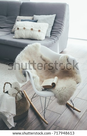 Still life details of living room. Sheep skin rug on modern armchair by the sofa with cushions. Reading book on the rocket chair. Cozy winter scene in Scandinavian interior.