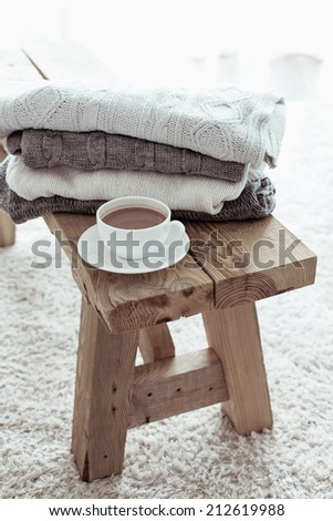 Still life details, stack of winter sweaters on rustic bench on white carpet - stock photo