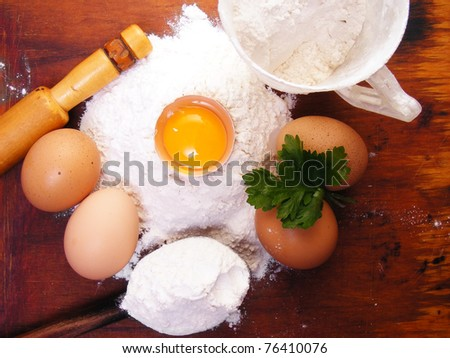 Still life eggs, flour and kitchen tools on a wooden board